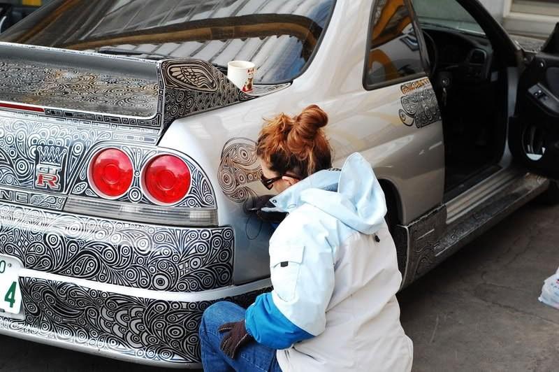 فنانة تستخدم قلم خطاط لاطلاء سيارة نيسان سكاي لاين