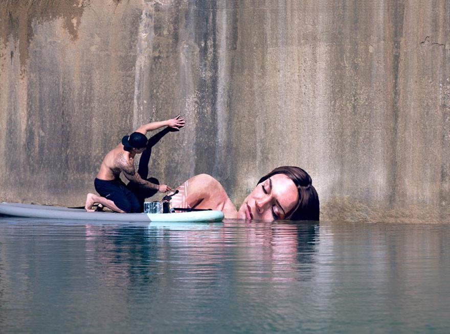 فنان يرسم لوحات جدارية مذهلة واقفا على لوح تزلج